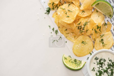 Photo for Top view of potato chips with salt near sliced lime and garlic sauce on white - Royalty Free Image