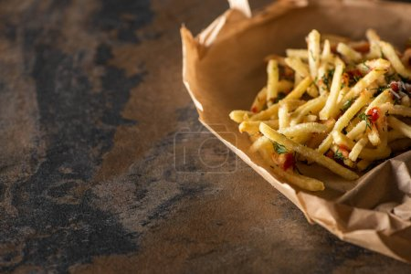 Photo for Tasty french fries with ketchup on baking paper and marble surface - Royalty Free Image