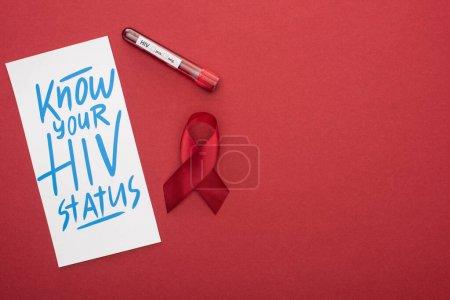 Photo pour Vue du haut de la carte avec votre inscription sur le statut sérologique du VIH et ruban de sensibilisation avec échantillon de sang sur fond rouge - image libre de droit