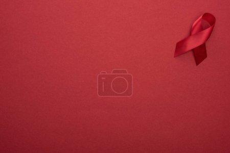 Photo pour Vue du dessus du ruban rouge des aides à la sensibilisation sur fond rouge - image libre de droit
