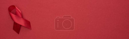 Photo for Top view of red awareness aids ribbon on red background, panoramic shot - Royalty Free Image