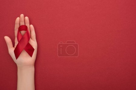 Photo for Cropped view of woman holding red awareness aids ribbon on red background - Royalty Free Image