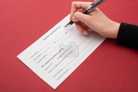 Photo pour Vue partielle de la femme remplissant le formulaire de résultat rapide du test du VIH sur fond rouge - image libre de droit