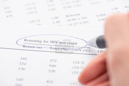 Photo pour Vue recadrée de la femme marquant le retour pour le test VIH formulaire de résultat avec stylo - image libre de droit