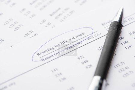 Photo pour Vue rapprochée du formulaire de retour pour le test de dépistage du VIH avec stylo - image libre de droit