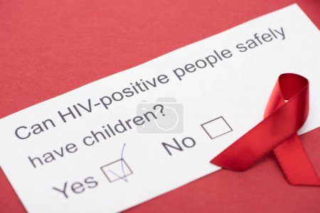 paper card with HIV questionnaire with awareness ribbon on red background