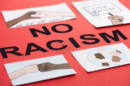 Photo for Black no racism lettering among pictures with multiethnic hands on red background - Royalty Free Image