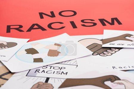 Photo pour Noir aucun lettrage de racisme parmi les images avec des mains multiethniques sur fond rouge - image libre de droit