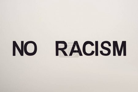 Photo pour Top view of black no racism lettering isolated on white - image libre de droit