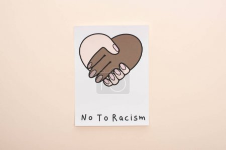Photo for Top view of picture with multiethnic handshake and no to racism lettering on beige background - Royalty Free Image
