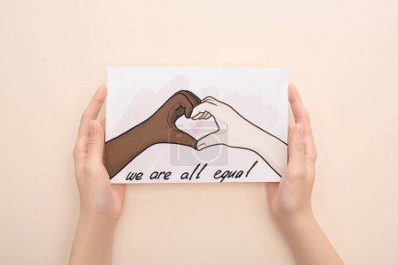 Foto de Visión rota de la mujer que tiene una imagen con manos multiétnicas dibujadas mostrando gesto cardíaco sobre un fondo beige. - Imagen libre de derechos