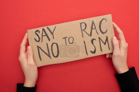 Photo for Cropped view of woman holding carton placard with say no to racism lettering on red background - Royalty Free Image