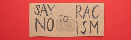 vista superior del cartel de cartón con decir no a las letras del racismo en el fondo rojo, plano panorámico