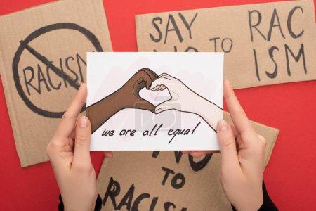 Foto de Vista recortada de la mujer que sostiene la imagen con manos multiétnicas dibujadas mostrando gesto cardíaco en el fondo rojo con pancartas. - Imagen libre de derechos