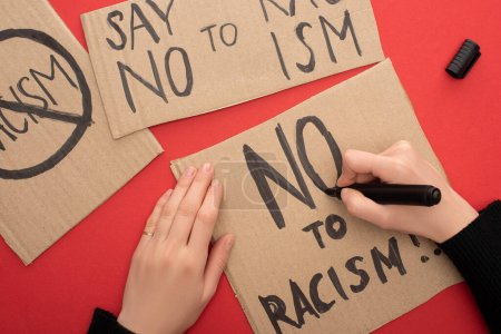 Photo for Cropped view of woman writing no to racism lettering with marker on carton placard on red background - Royalty Free Image