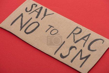 Photo pour Plaque en carton avec dire non au lettrage raciste sur fond rouge - image libre de droit