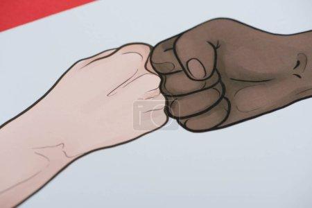 imagen con manos multiétnicas dibujadas haciendo golpe de puño sobre fondo rojo