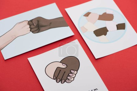 close up view of pictures with multiethnic hands on red background