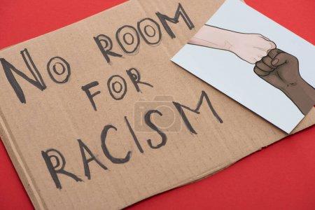 cartel de cartón con decir que no hay espacio para letras de racismo y la imagen con las manos multiétnicas dibujadas haciendo golpe de puño sobre el fondo rojo