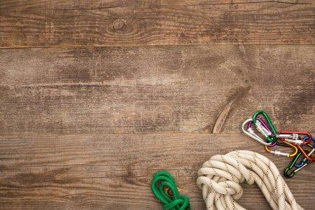 Photo pour Vue de dessus des cordes de randonnée et des mousquetons sur la table en bois - image libre de droit