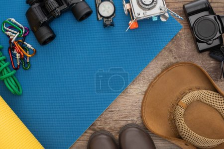 top view of hiking equipment on blue sleeping mat, photo camera, boots and hat on wooden surface