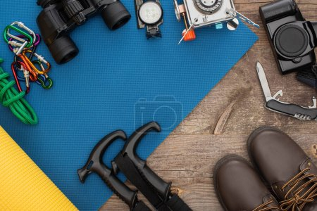 Photo for Top view of hiking equipment on blue sleeping mat, photo camera and boots on wooden table - Royalty Free Image