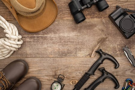 Photo for Top view of hiking equipment, boots, hat and photo camera on wooden surface - Royalty Free Image