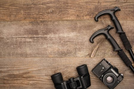 Photo for Top view of binoculars, phote camera and trekking poles on wooden surface - Royalty Free Image