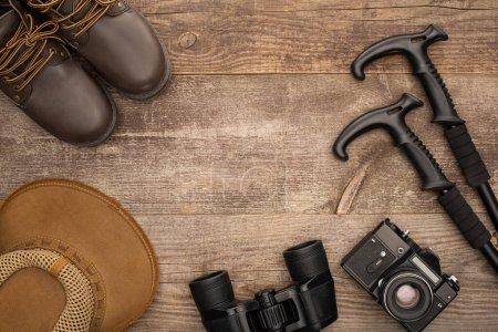 Photo pour Vue de dessus des bottes, chapeau, jumelles, appareil photo et bâtons de trekking sur la surface en bois - image libre de droit