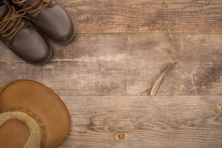 Photo for Top view of brown boots and hat on wooden surface - Royalty Free Image