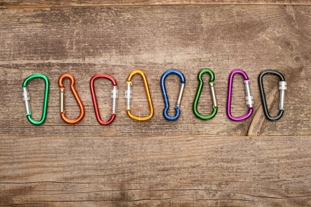 Photo for Top view of colorful carabiners in row on wooden table - Royalty Free Image