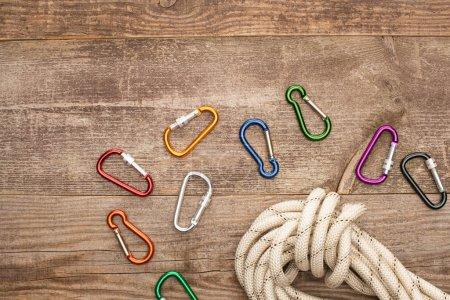 Photo pour Vue de dessus de mousquetons colorés et corde de randonnée sur table en bois - image libre de droit