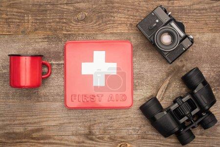 Photo pour Vue du dessus de la trousse de premiers soins, appareil photo, jumelles et tasse en métal rouge sur une table en bois - image libre de droit