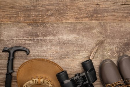 Photo for Top view of trekking pole, hat, boots and binoculars on wooden table - Royalty Free Image