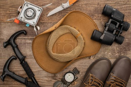 Photo for Top view of hat, boots, hiking poles, binoculars, jackknife and gas-burner on wooden surface - Royalty Free Image