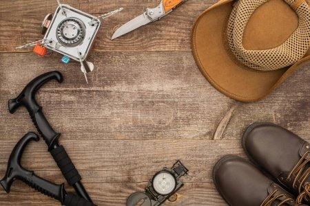Photo for Top view of trekking poles, gas burner, jackknife, hat, boots and compass on wooden table - Royalty Free Image
