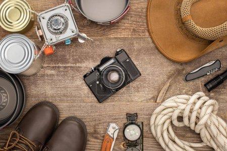 Photo pour Vue de dessus de l'appareil photo, chapeau, bottes et matériel de randonnée sur table en bois - image libre de droit
