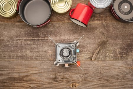 Photo for Top view of tin cans, gas-burner, metal dishes and cup on wooden surface - Royalty Free Image