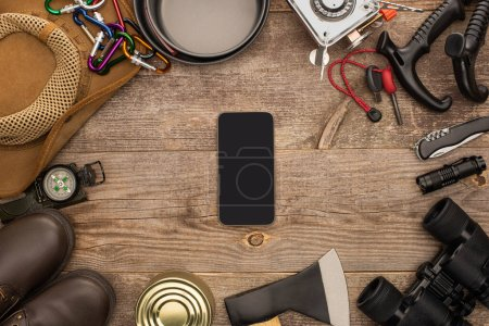 top view of smartphone with black screen near hiking equipment on wooden table