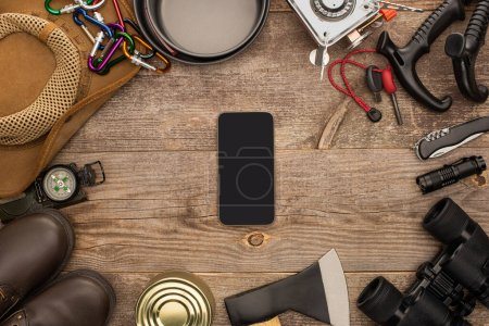 Photo for Top view of smartphone with black screen near hiking equipment on wooden table - Royalty Free Image