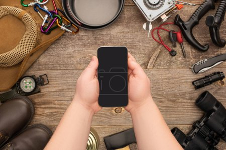 Photo for Partial view of man holding smartphone with blank screen over hiking equipment on wooden table - Royalty Free Image