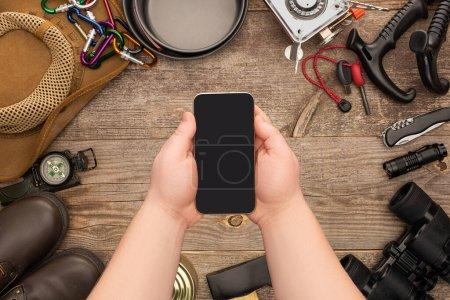 Photo pour Vue partielle d'un homme tenant un smartphone avec écran blanc sur un équipement de randonnée sur une table en bois - image libre de droit