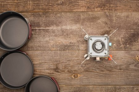 Photo for Top view of gas burner and camping dishes on wooden table - Royalty Free Image