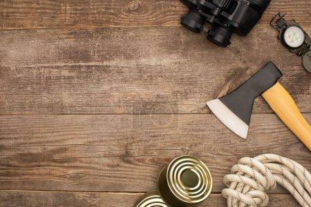 Photo pour Vue de dessus de hache, boîtes de conserve, corde de randonnée, boussole et jumelles sur la surface en bois - image libre de droit