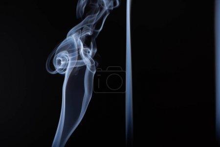 white flowing smoke on black background with copy space