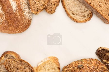 Photo for Top view of fresh brown bread slices and loaves on white background - Royalty Free Image