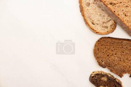 Photo pour Vue de dessus des tranches de pain de grains entiers frais sur fond blanc - image libre de droit