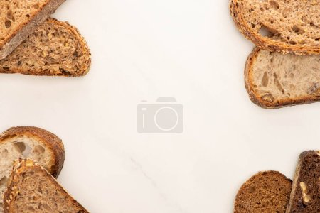 Photo for Top view of fresh whole grain bread slices on white background with copy space - Royalty Free Image
