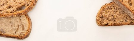 Photo for Top view of fresh whole grain bread slices on white background with copy space, panoramic shot - Royalty Free Image