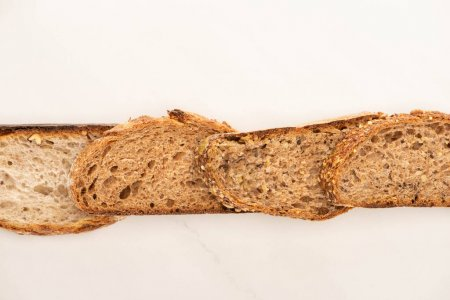 top view of whole grain bread slices in line on white background